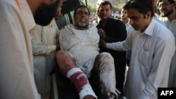 Pakistani paramedics shift an injured man into the hospital after a suicide blast in Mardan at the gathering of funeral prayers, in Peshawar, June 18, 2013.