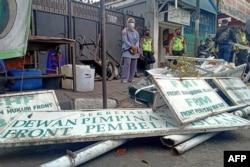 Polisi membongkar papan nama di markas besar organisasi garis keras Indonesia FPI (Front Pembela Islam atau Front Pembela Islam) di Jakarta pada 30 Desember 2020, setelah pemerintah melarang kelompok itu melakukan kegiatan apa pun. (Foto: DANY K./AFP)