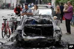 Un auto quemado por manifestantes es observado por varias personas en Hamburgo, Alemania, en el primer día de la Cumbre del G20. Julio 7 de 2017.
