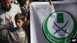 """An Egyptian boy holds a banner with Arabic that reads, """"Muslim Brotherhood,"""" in Cairo, Egypt, Nov. 15, 2012."""