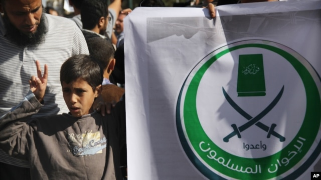 "An Egyptian boy holds a banner with Arabic that reads, ""Muslim Brotherhood,"" in Cairo, Egypt, Nov. 15, 2012."