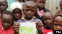 Children pose for a photo at the Bethel Outreach Children's Center in the Nairobi slum of Kibera as one boy holds up his Peepoo toilet, April 4, 2012. Toilet facilities are in poor condition or nonexistent in the slums, and safety concerns make using a to