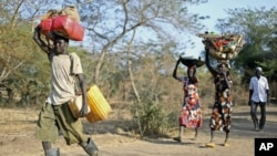 A Sudanese family from the war-torn Blue Nile state carry their belongings on their heads as they arrive at South Sudan's Doro refugee camp December 12, 2011.