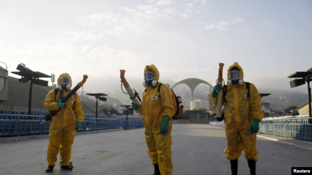 FILE - Municipal workers wait before spraying insecticide at Sambodrome in Rio de Janeiro, Brazil, Jan. 26, 2016.