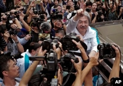 FILE - Chief Executive candidate, Hong Kong's former Financial Secretary John Tsang, center, waves to supporters at an election campaign in Hong Kong, March 24, 2017.