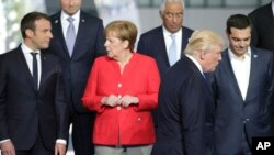File - French President Emmanuel Macron, left, speaks with German Chancellor Angela Merkel, second left, as President Trump takes his position during a group photo at the new NATO headquarters in Brussels on Thursday, May 25, 2017.