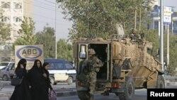 کابل میں ایک حملے کے بعد جائے واقعہ پر تعینات برطانوی فوجیوں کے نزدیک سے افغان خواتین گزر رہی ہیں۔