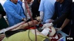 En primer plano el fotógrafo Chris Hondros, cuando era retirado herido de gravedad tras el ataque que le causó la muerte horas después.