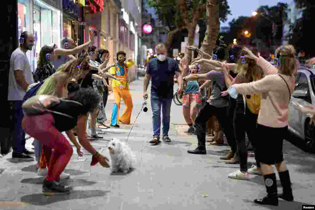 A man wears a mask and walks his dog past people taking part in a silent disco event as some businesses reopened at the end of last month following weeks of shutdown amid the coronavirus disease (COVID-19) crisis, in Tel Aviv, Israel.