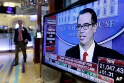 Treasury Secretary Steven Mnuchin appears on a television screen on the floor of the New York Stock Exchange, April 26, 2017.