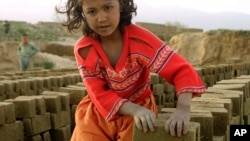 FILE - An Afghan girl makes a pile of unbaked bricks near the road passing through the Shamali Plains, about 10 kilometers ( 6 miles), west of Bagram, Afghanistan.
