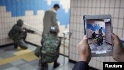 Seorang pria memotret tentara-tentara Korea Selatan dengan iPadnya pada saat latihan anti-teror dan keamanan di stasiun bawah tanah di Seoul, April 2013. (Reuters/Kim Hong-Ji)