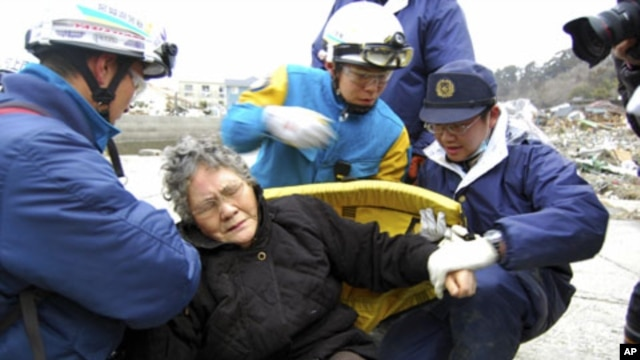 Eighty-year-old Sumi Abe is helped by emergency workers after being rescued from under the rubble in Ishinomaki City, Miyagi Prefecture, northern Japan, March 20 , 2011
