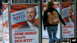 """A woman walks past election posters of Norbert Hofer, candidate for presidential elections of Austria's right-wing Freedom Party, FPOe, in Vienna, Austria, April 19, 2016. The posters read """"Your country needs you now."""""""