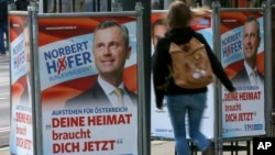 "A woman walks past election posters of Norbert Hofer, candidate for presidential elections of Austria's right-wing Freedom Party, FPOe, in Vienna, Austria, April 19, 2016. The posters read ""Your country needs you now."""