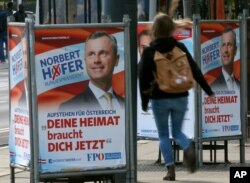 FILE - A woman walks past election posters of Norbert Hofer, candidate for presidential elections of Austria's right-wing Freedom Party, FPO, in Vienna, Austria, April 19, 2016.