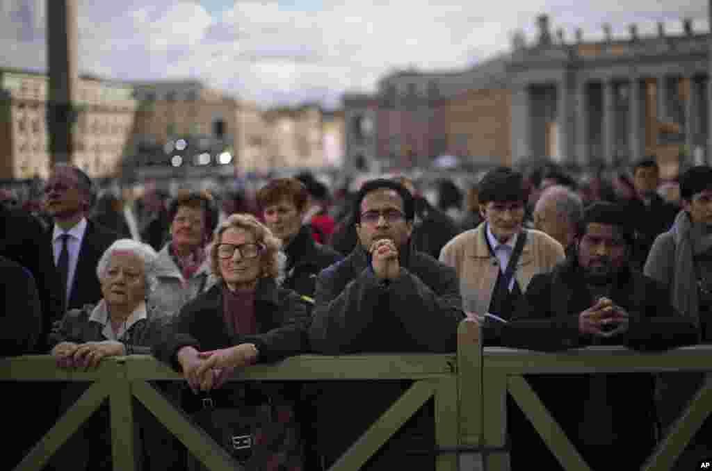 Faithful follow a Mass taking place inside St.Peter's Basilica for the election of a new pope, broadcast on a giant screen, not pictured, in St. Peter's Square, at the Vatican, March 12, 2013.