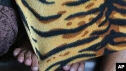 Tersangka yang ditangkap dalam operasi gabungan terhadap pornografi anak bersembunyi di balik selimut di Manila, Filipina. (Foto: ilustrasi)