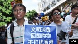 新同盟荃灣區議員譚凱邦手持簡體字標語,呼籲中國旅客不要來香港購物。(美國之音湯惠云)