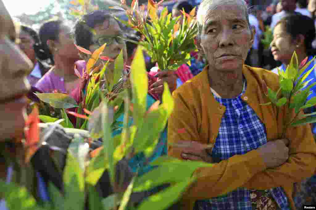 Family members hold leaves as they wait for political prisoners to be released from Insein prison in Rangoon, Burma, Dec. 31, 2013.