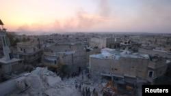 叙利亚反叛武装控制的阿勒颇的哈拉克附近,人们检查空袭带来的破坏。