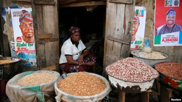 FILE - Latefat Alao, 56, a ethnic Yoruba Muslim woman, waits for customers in front of her in Beere market in Ibadan, southwest Nigeria, Jan. 29, 2015.