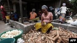 Une femme épluche des couches extérieures de manioc pour le plat d'accompagnement, attiéké, à Abidjan, le 22 mai 2018.