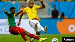Brazil's Fernandinho (R) shoots to score past Cameroon's Nicolas Nkoulou during their 2014 World Cup Group A soccer match at the Brasilia national stadium in Brasilia, June 23, 2014.