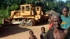 Congolese people standing in front of two bulldozers in Yayolo, Democratic Republic of Congo, October 2004. (file photo)