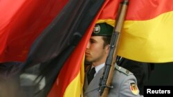 ARHIVA - Nemački vojnik ispod nacionalne zastave, u Berlinu, 14. septembra 2006. (Foto: Reiters/Fabrizio Bensch)
