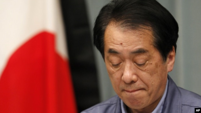 Japan's Prime Minister Naoto Kan in front of the Japanese flag with a black mourning cloth during a news conference at his official residence in Tokyo, March 25, 2011.