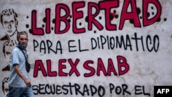 """FILE - A man walks past graffiti reading, """"Freedom for diplomat Alex Saab, kidnapped by the government of Cape Verde,"""" in Caracas, Venezuela, Feb. 23, 2021. A Cape Verde court on Aug. 30 upheld a decision to extradite Saab to the U.S."""