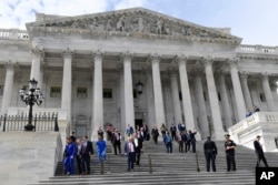Members of the House of Representatives walk down the steps of Capitol Hill in Washington, March 27, 2020, after passing a coronavirus rescue package.