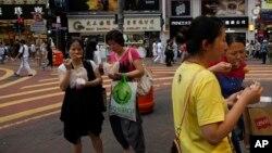 Para turis dari China daratan memakan jajanan pinggir jalan di pusat kota Hong Kong. (Foto: Dok)