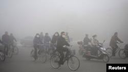 Warga setempat melintasi jalanan yang tertutup kabut tebal akibat polusi di Daqing, provinsi Heilongjiang (21/10).