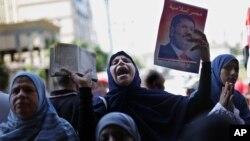 Para pendukung Presiden terguling Mohamed Morsi meneriakkan slogan dan memegang poster mantan presiden tersebut dalam protes di Lapangan Giza, Mesir (23/8).