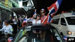 Thai anti-government protesters wave national flags as they follow march through streets of Bangkok, Dec. 20, 2013.