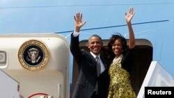ປະທານາທິບໍດີສະຫະລັດ ທ່ານບາຣັກ ໂອບາມາ ແລະສະຕີໝາຍເລກນຶ່ງ ທ່ານນາງ Michelle ໂບກມືຈາກເຮືອບິນ Air Force One ຂະນະທີ່ພວກທ່ານ ອອກຈາກສະໜາມບິນ ນະຄອນ Dakar ປະເທດເຊເນກາລ (28 ມິຖຸນາ 2013)