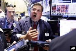 Trader John Santiago, center, works on the floor of the New York Stock Exchange, Aug. 24, 2015.