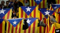 FILE - F.C Barcelona supporters wave Estelada or pro-independence flags. Catalonian lawmakers are due to vote on a measure to begin a secession process on Monday.