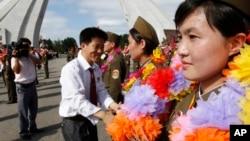 지난 2012년 8월 북한 백두산에서 청년절을 앞두고 성화 봉송 행사가 열린 가운데, 행사에 참석한 군인들이 대학생들로부터 화환을 받고 있다. (자료사진)