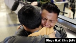 In this Wednesday, Jan. 22, 2020, file photo, David Xol-Cholom, of Guatemala, hugs his son Byron at Los Angeles International Airport as they reunite after being separated during the Trump administration's wide-scale separation of immigrant families.