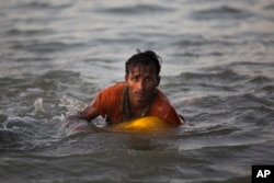 Rohingya Muslim Abdul Karim, 19, uses a yellow plastic drum as a floatation device as he swims the Naf River to Bangladesh in Shah Porir Dwip, Nov. 4, 2017. Some have never been in the water before.