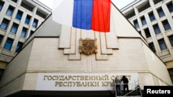 우크라이나 크림자치공화국이 독립을 선언한 가운데, 19일 심페로폴 의회에서 현판을 수정하고 있다.