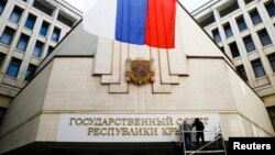 Các công nhân lắp biển chữ mới 'Hội đồng Nhà nước Cộng hoà Crimea' tại toà nhà quốc hội ở Simferopol, 19/3/2014.