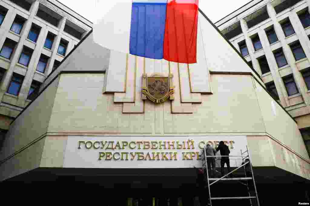 "Workers put up a new sign reading ""State Council of the Crimean Republic"" at the parliament building in Simferopol, March 19, 2014."