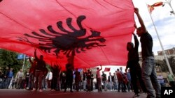 FILE - Ethnic Albanians hold a large Albanian flag during a protest by ethnic Albanian civic organizations and several minor political parties in front of the parliament building in Skopje, Macedonia, demanding the establishment of the rule of law, April 22, 2016.