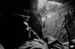 An East Pakistan (present-day Bangladesh) soldier uses a field telephone in a bunker as another soldier peers inside, near Jessore, East Pakistan, Dec. 3, 1971. The Pakistani soldiers had been shelled by Indian artillery.