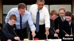 El primer ministro David Cameron (segundo de la izquierda) y el presidente Barack Obama pintan junto a estudiantes de la escuela primaria Enniskillen en Irlanda del Norte.