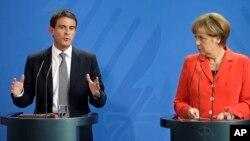 PM Perancis Manuel Valls (kiri) dan Kanselir Jerman Angela Merkel memberikan konferensi pers bersama di Berlin hari Senin (22/9).